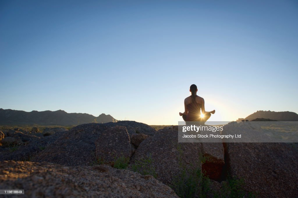 Hispanic woman practicing yoga on rock : Stock Photo
