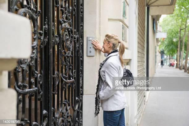 hispanic woman pressing buzzer on city street - intercom stock photos and pictures