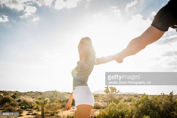 hispanic woman pulling arm of man in desert - mid section stock photos and pictures