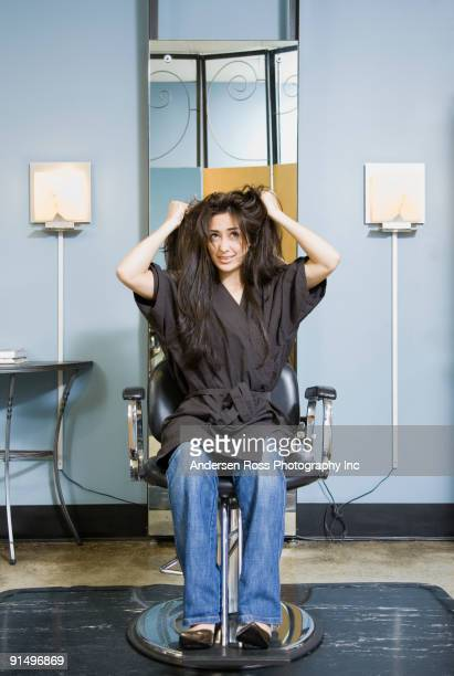 Hispanic woman pulling on hair in salon