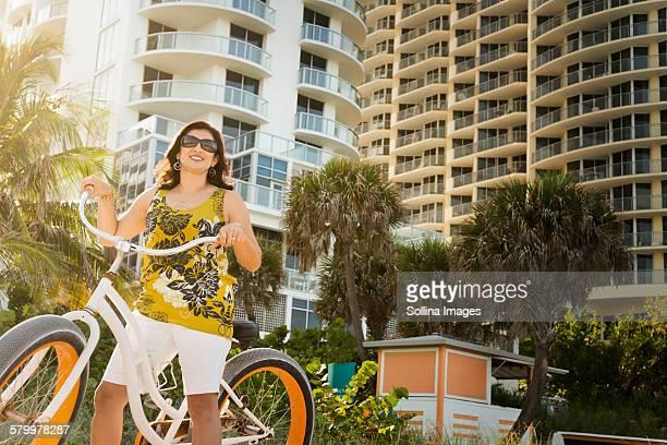 Hispanic woman pushing bicycle in city
