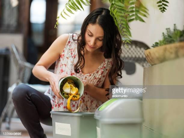 femme hispanique mettant le gaspillage organique dans le bac - humus photos et images de collection
