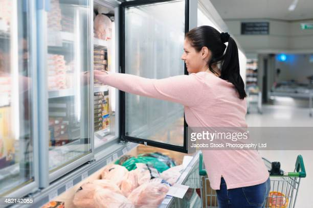 Hispanic woman reaching in frozen food case in supermarket