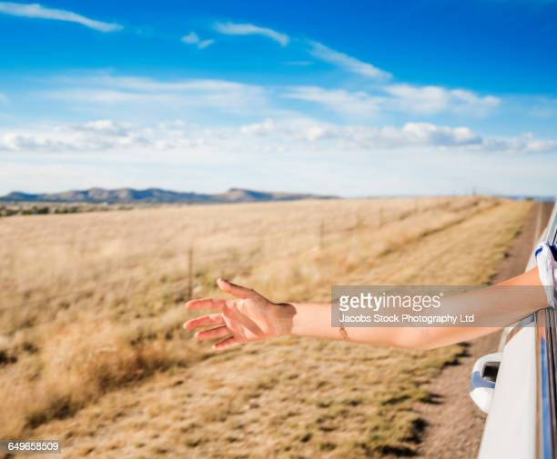 hispanic woman reaching out car window - arms outstretched stock pictures, royalty-free photos & images