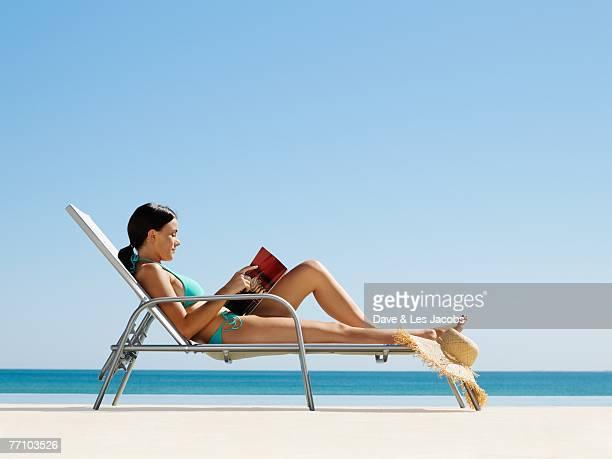 Hispanic woman reading at beach