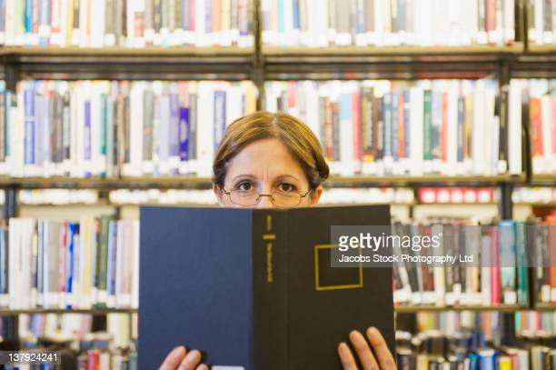 Hispanic woman reading book in library