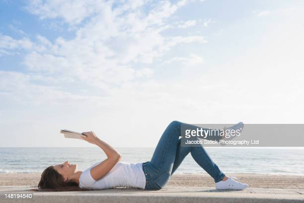 hispanic woman reading book on beach - lying down fotografías e imágenes de stock