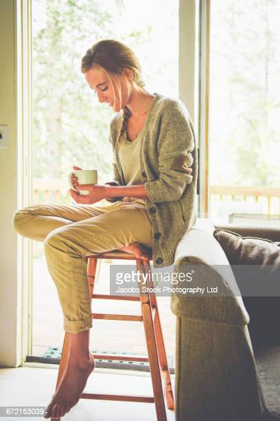 Hispanic woman reading book on livingroom stool