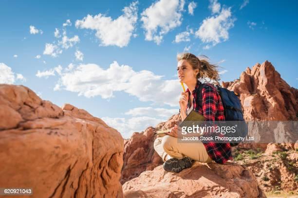 Hispanic woman reading book on rock formation