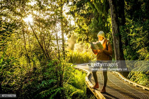 Hispanic woman reading map on winding footbridge in forest