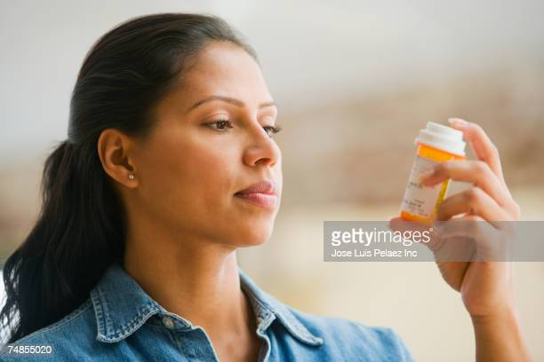 hispanic woman reading medication - dosis stock-fotos und bilder
