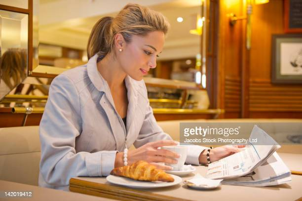 Hispanic woman reading paperwork and having breakfast in cafe