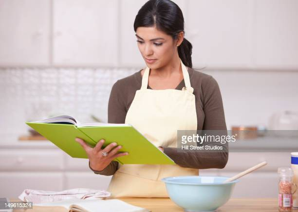 hispanic woman reading recipe in kitchen - caderno de receitas - fotografias e filmes do acervo