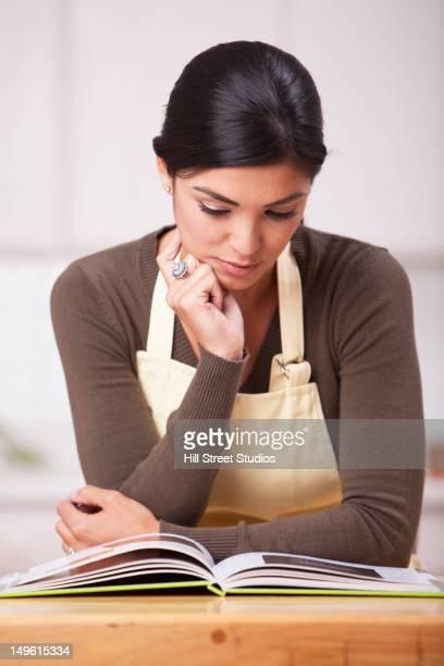 hispanic woman reading recipe in kitchen - gardena california stock pictures, royalty-free photos & images