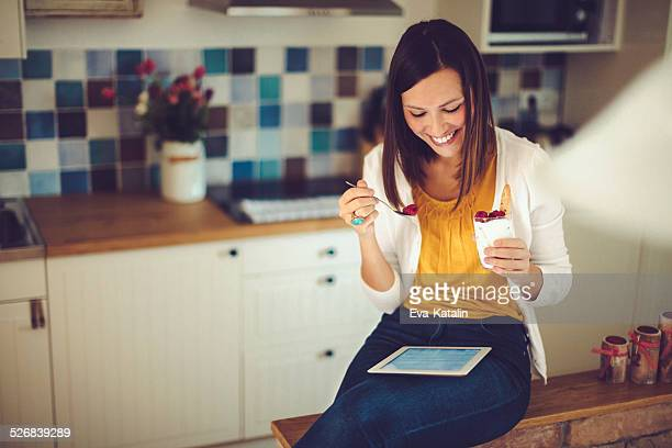 Hispanic woman reading tablet and having breakfast in the kitchen