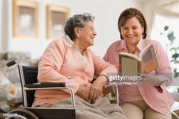 hispanic woman reading to mother - visit stock pictures, royalty-free photos & images