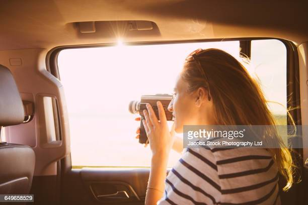 Hispanic woman recording out car window