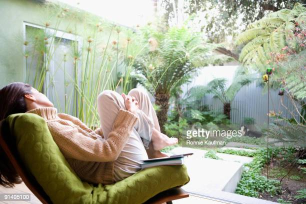 Hispanic woman relaxing in chair