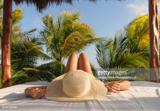 Hispanic woman relaxing in hut on beach