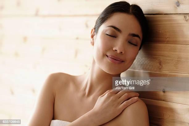 Hispanic woman relaxing in sauna