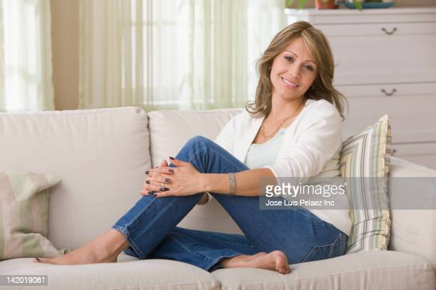 hispanic woman relaxing on sofa - hugging knees stock pictures, royalty-free photos & images