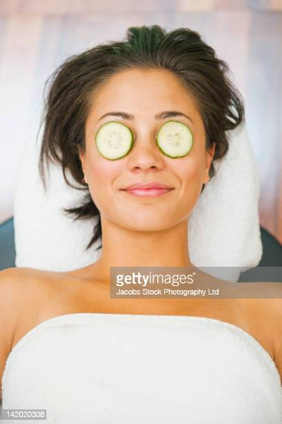 Hispanic woman relaxing with cucumbers on her eyes