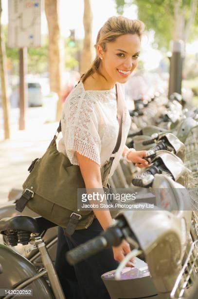 Hispanic woman renting bicycle