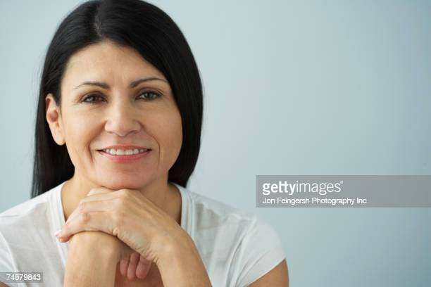 hispanic woman resting chin on hands - 40 49 years stock pictures, royalty-free photos & images