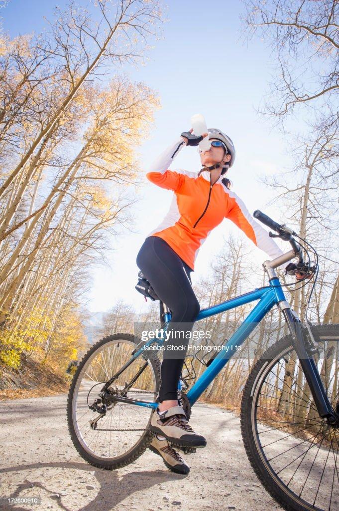 Hispanic woman riding dirt bike on path : Stock Photo