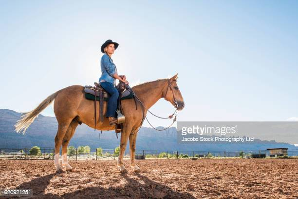 hispanic woman riding horse on ranch - adults only stock pictures, royalty-free photos & images