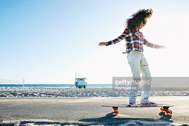 hispanic woman riding skateboard at beach - candid beach stock photos and pictures