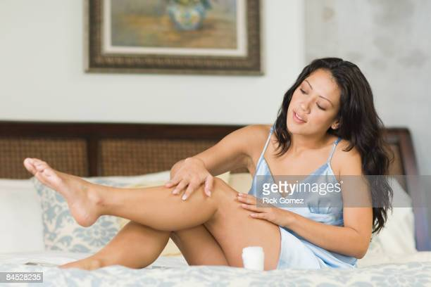 hispanic woman rubbing lotion on legs in bedroom - women in slips stock photos and pictures
