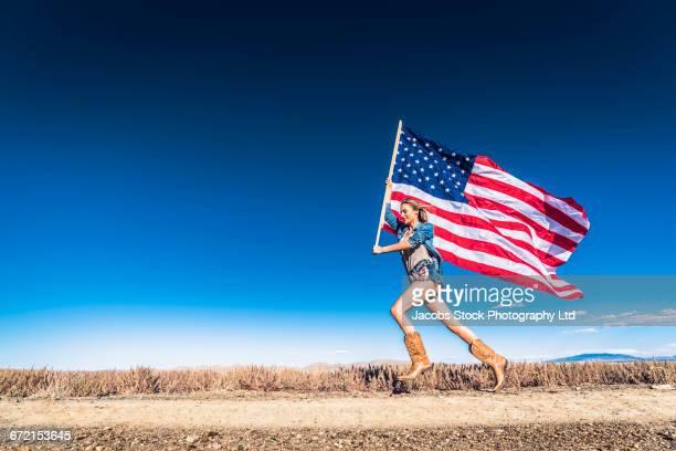 Hispanic woman running in desert carrying American flag