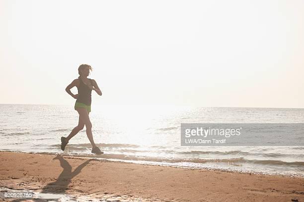 Hispanic woman running on beach