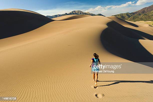 hispanic woman running on sand dune - great sand dunes national park stock pictures, royalty-free photos & images