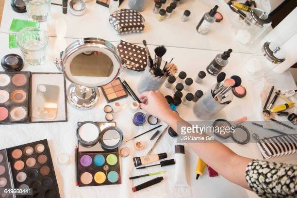 Hispanic woman selecting makeup from table