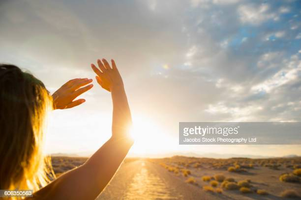 Hispanic woman shielding eyes from sun on remote road