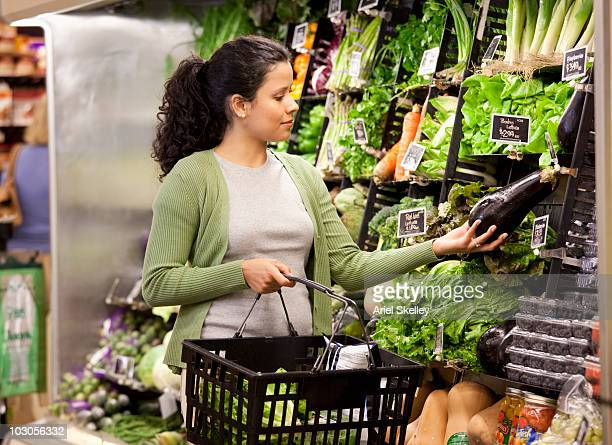 Hispanic woman shopping for fresh vegetables