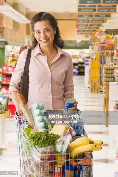 hispanic woman shopping in grocery store - caddie rempli photos et images de collection