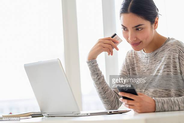 Hispanic woman shopping on cell phone and laptop