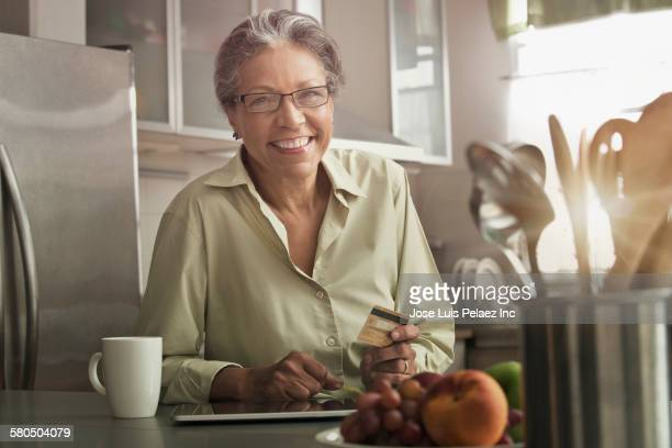 Hispanic woman shopping on digital tablet in kitchen