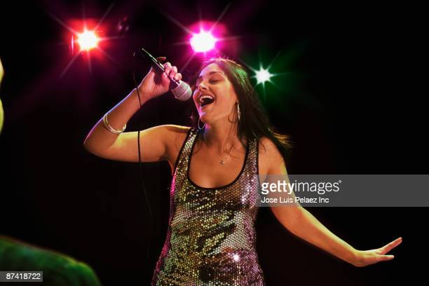 hispanic woman singing in nightclub - the weekend singer stock pictures, royalty-free photos & images