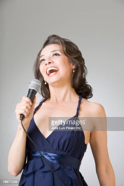 Hispanic woman singing into microphone