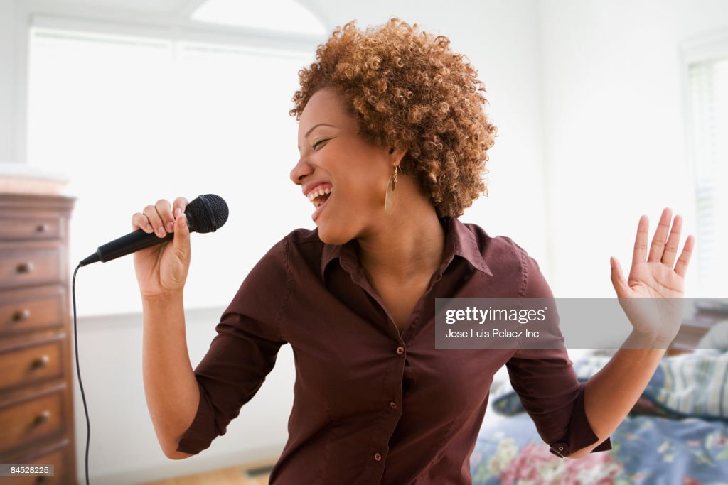 Hispanic woman singing on microphone in bedroom : Stockfoto