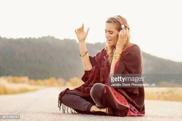 Hispanic woman singing with headphones in middle of street