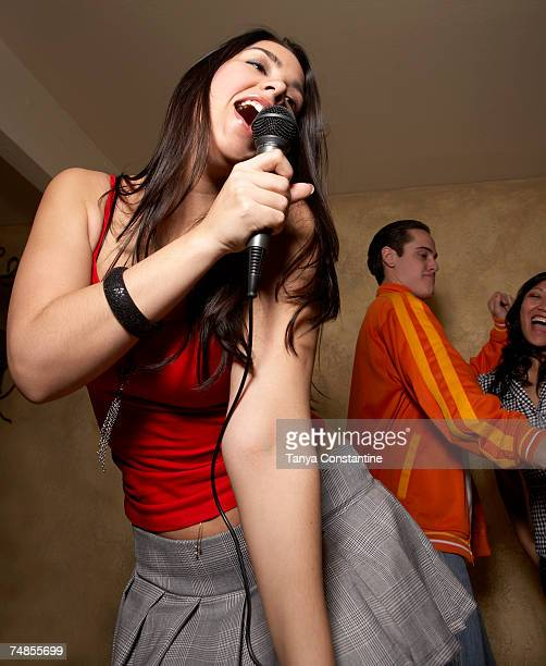 Hispanic woman singing with microphone