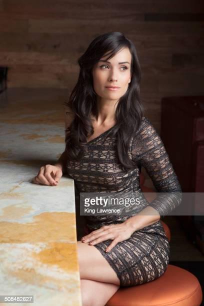 hispanic woman sitting at bar - verführerische frau stock-fotos und bilder