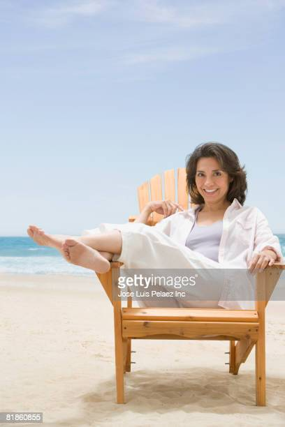 hispanic woman sitting at beach - one mature woman only stock pictures, royalty-free photos & images