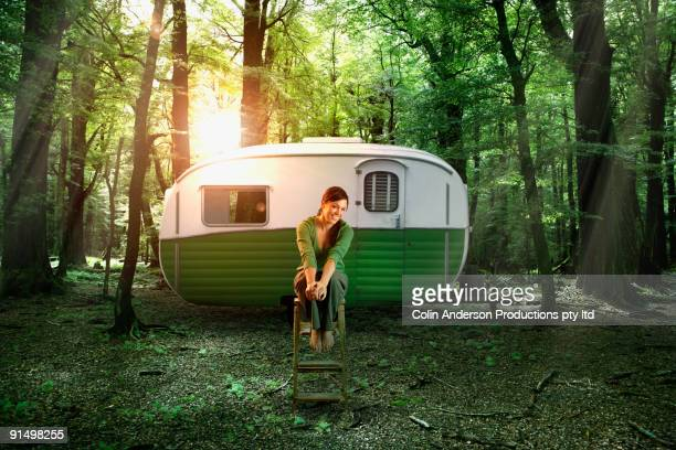Hispanic woman sitting by camper in forest