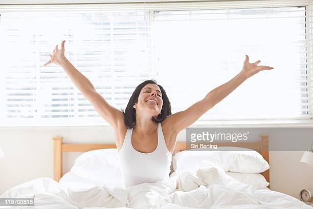Hispanic woman sitting in bed with arms raised